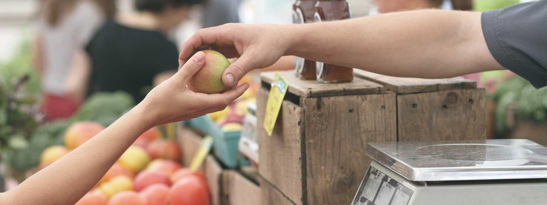 Eine Frauenhand ist zu sehen, die an einem Marktstand einen Apfel aus der Hand eines Mannes nimmt, der ihn ihr über den Obststand reicht.